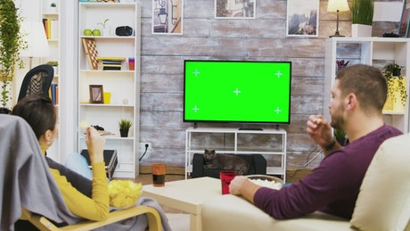 Couple watching green screen TV and eating popcorn