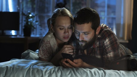 Couple watching the smartphone in the bed
