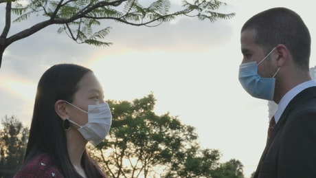 Couple wearing face masks under a beautiful sunset