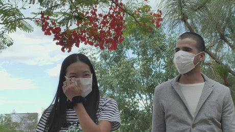 Couple with masks walking in a park