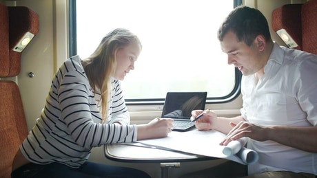Couple working during a train journey