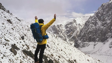 Courageous hiker spreads arms over mountain summit