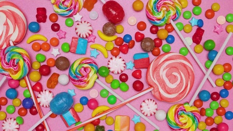 Covering a pink background with candies in stop motion