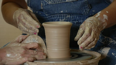 Craftsman women shaping a clay vase