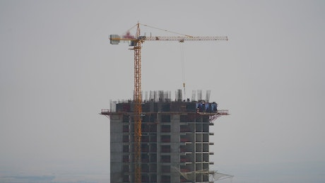 Crane and construction workers at the top of a building
