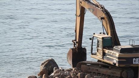 Crane digging on rocks at the sea