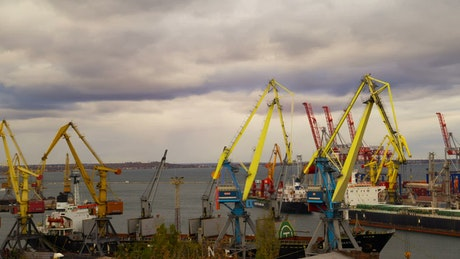 Cranes at seaport working on a cloudy day