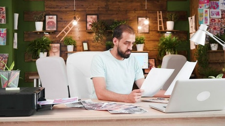 Creative man prints out ideas in home office