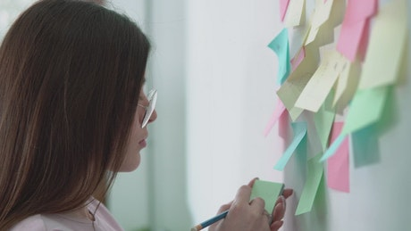 Creative woman writing ideas on sticky notes for marketing project