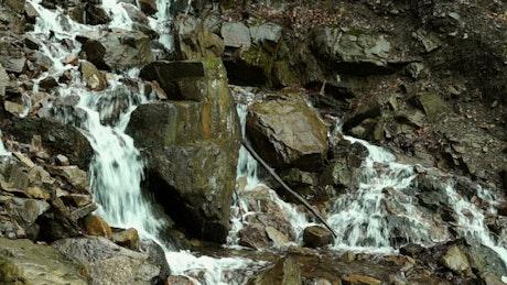 Creek flowing through the mountain rocks