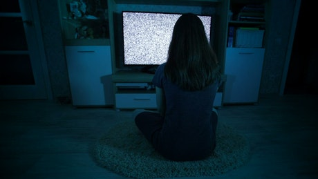 Creepy woman looking at static on a TV