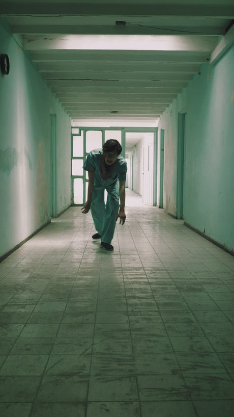 Creepy zombie male nurse approaching down a hallway