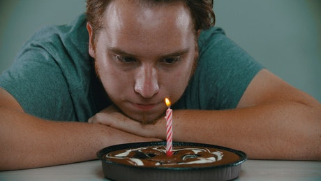 Crestfallen man blowing out the candle on a cake