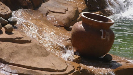 Crock pot atop a small rock waterfall