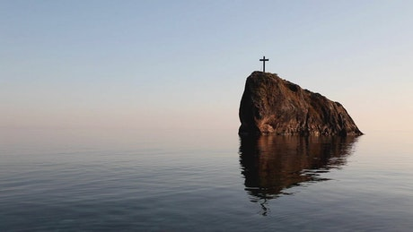 Crucifix on a cliff in the sea, landscape
