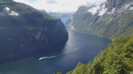 Cruise ship sailing between mountains