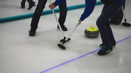 Curling stone players sweeping