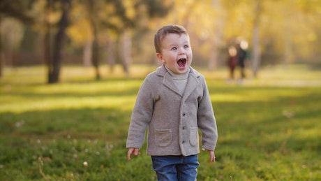 Cute boy surprised in a park, portrait