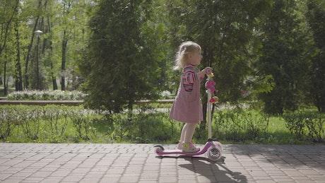 Cute little girl rides scooter down brick sidewalk