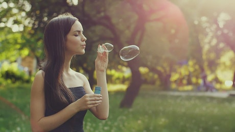Cute young woman blowing bubbles in the park