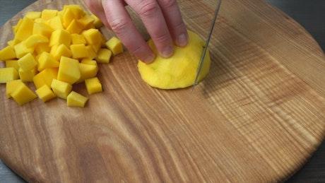 Cutting mango cubes on a board
