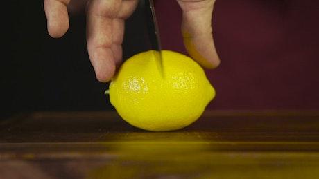 Cutting through a lemon with a knife