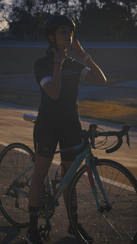 Cyclist girl putting on her helmet before training