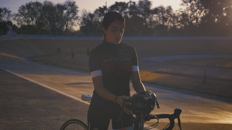 Cyclist putting on her helmet before training