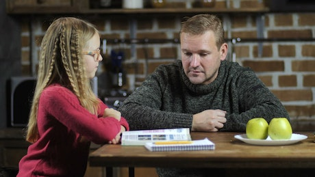 Dad teaching his young daughter to read