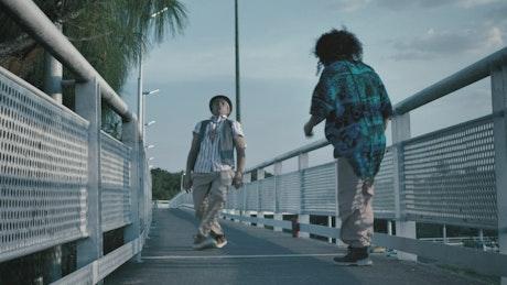 Dancing hip-hop on a pedestrian bridge