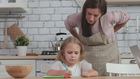 Daughter drawing in the kitchen with mom