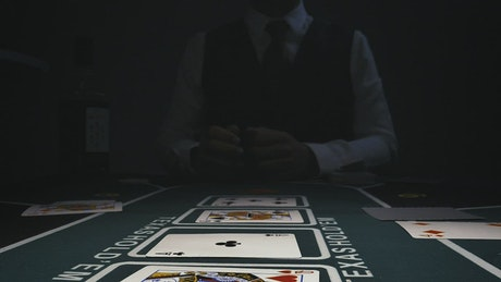 Dealer picking up cards from a gaming table