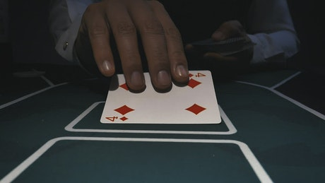 Dealer placing poker cards on a gaming table