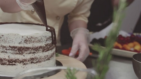 Decorating a cake with chocolate