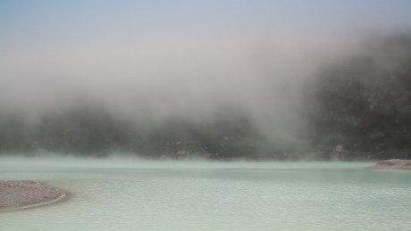 Deep fog descending across a lake