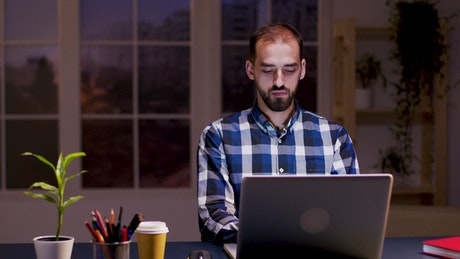 Deep thinking man working on laptop from home