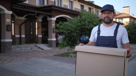 Delivery man carrying a large box
