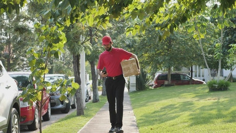 Delivery man looking for an address on the street