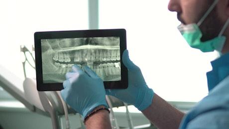 Dental nurse explains teeth X-ray on tablet