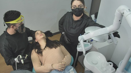 Dentist and his assistant working with a patient