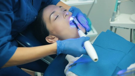 Dentist applying blue light to his patient