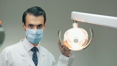 Dentist holding a lamp in his office