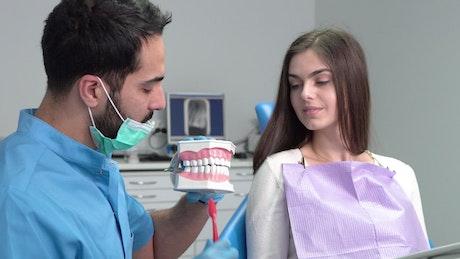 Dentist shows woman proper teeth brushing