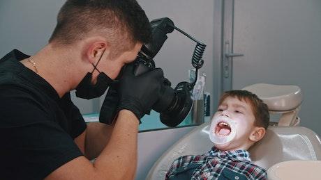Dentist taking photos of a little boy's teeth