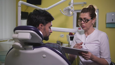 Dentist using a tablet while speaking