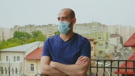 Depressd man in face mask on balcony crossing arms
