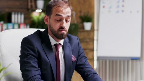 Depressed businessman rubs face and looks at report