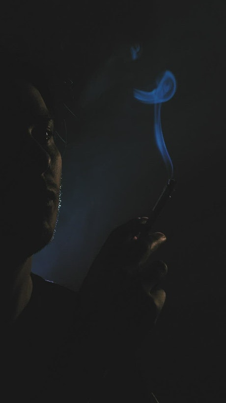 Depressed guy smoking in the dark