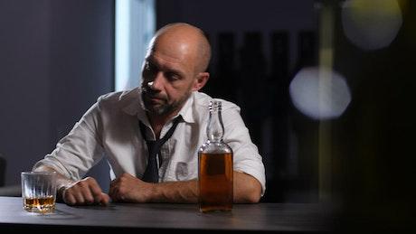 Depressed man drinking at a bar