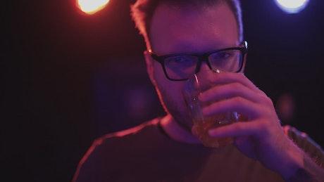 Depressed man drinking in a nightclub